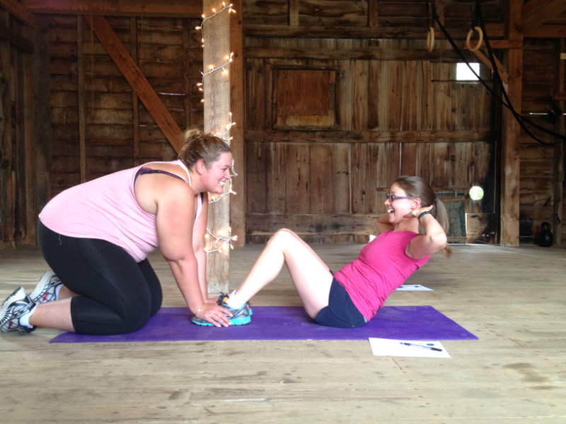 Kendra strikes a sit-up pose while my fellow bootcamper, Sarah, holds her feet.