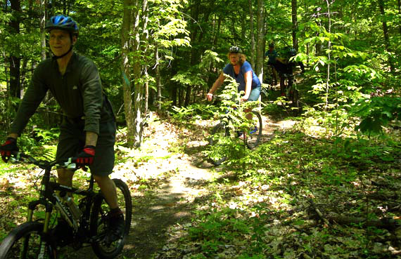 Cliff Krolick, owner of Back Country Excursions, and Liz Briggeman, novice mountain biker, tackle a mountain trail during a beginner's class back in 2009. Photo by Shannon Bryan