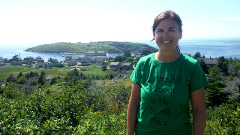 Tara Hire, founder of Monhegan Wellness, on the island cliffs with town, the dock and Manana Island in the background. Shannon Bryan photo