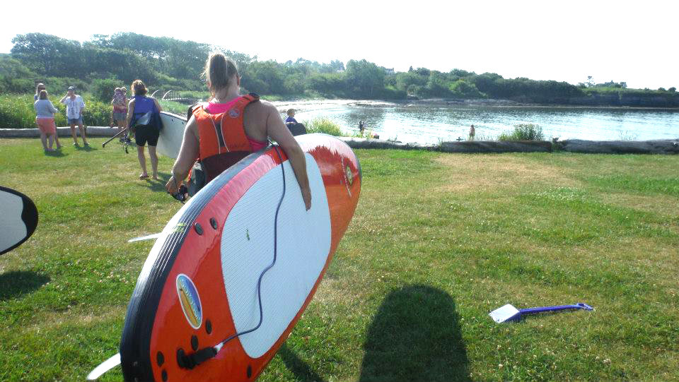 Beth carries her SUP, rented from SOPOSUP, down to the beach at Kettle Cove. Shannon Bryan photo