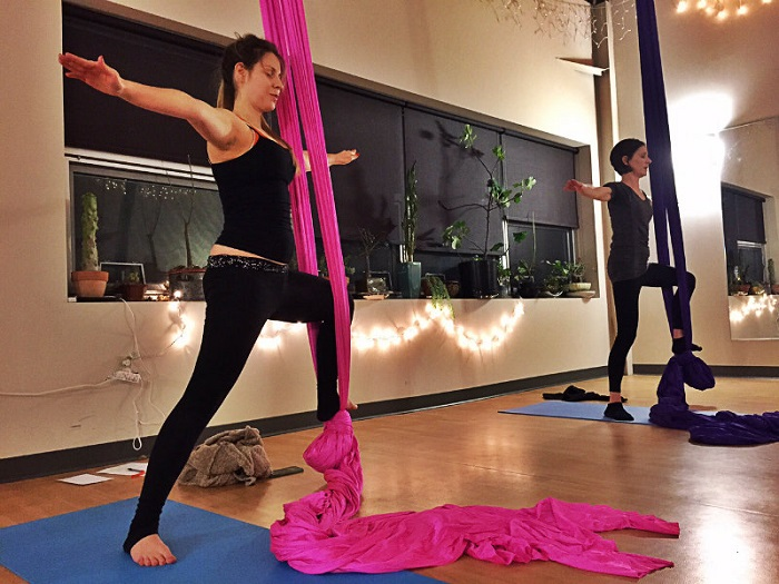 Instructor Hannah, on left, leads an aerial yoga class in warrior pose at Evo Rock + Fitness in Portland. Shannon Bryan photo