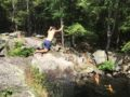 person in shorts jumping into swimming hole