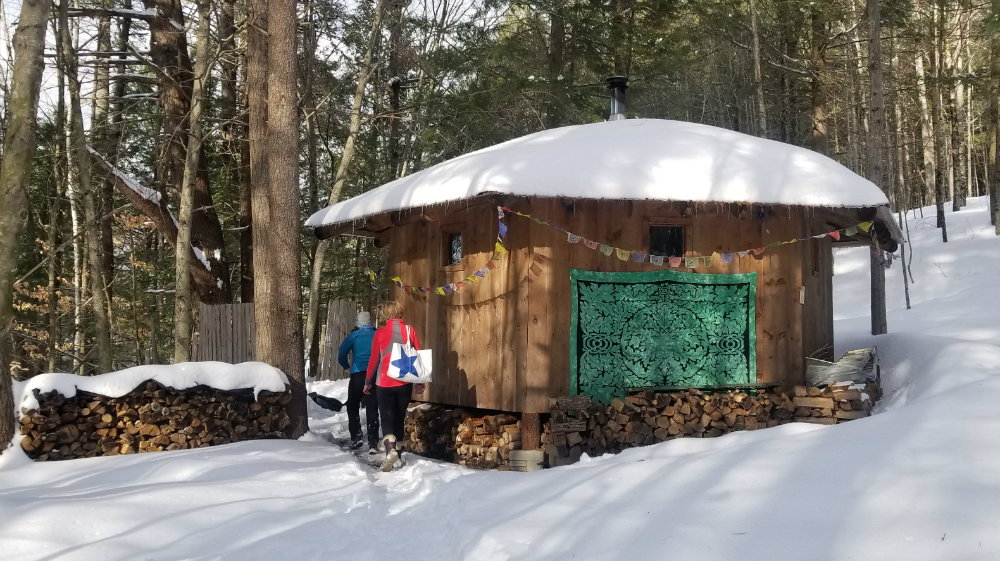 wood sauna set in the woods blanketed by fresh snow and sun shining through the trees