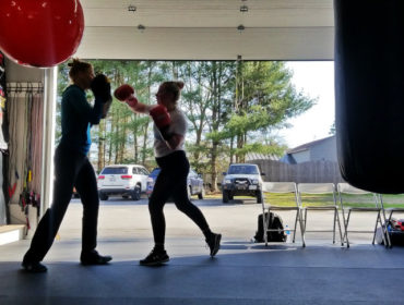 Two women boxing in garage