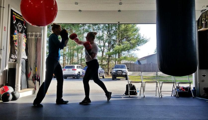 Two women boxing in garage
