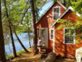 Woman walking out of cabin overlooking a stream