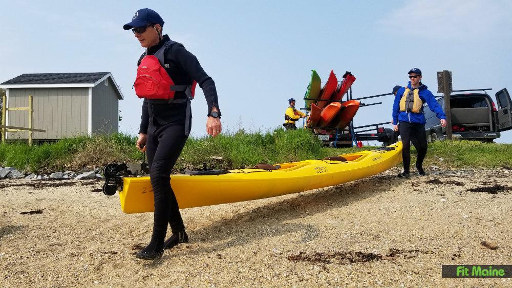 Two people carring kayak to water