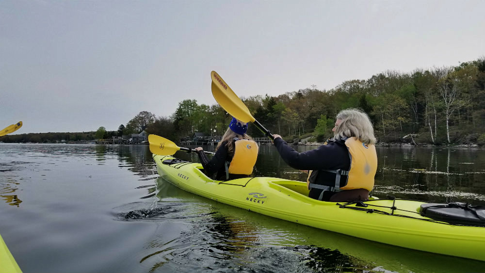 Two women kayaking in a tandem kayak off the coast of Maine