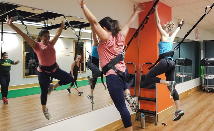 two women in a fly bungee class leaping toward mirror