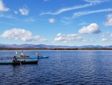 Kayakers paddle across lake with mountain and blue sky behind them