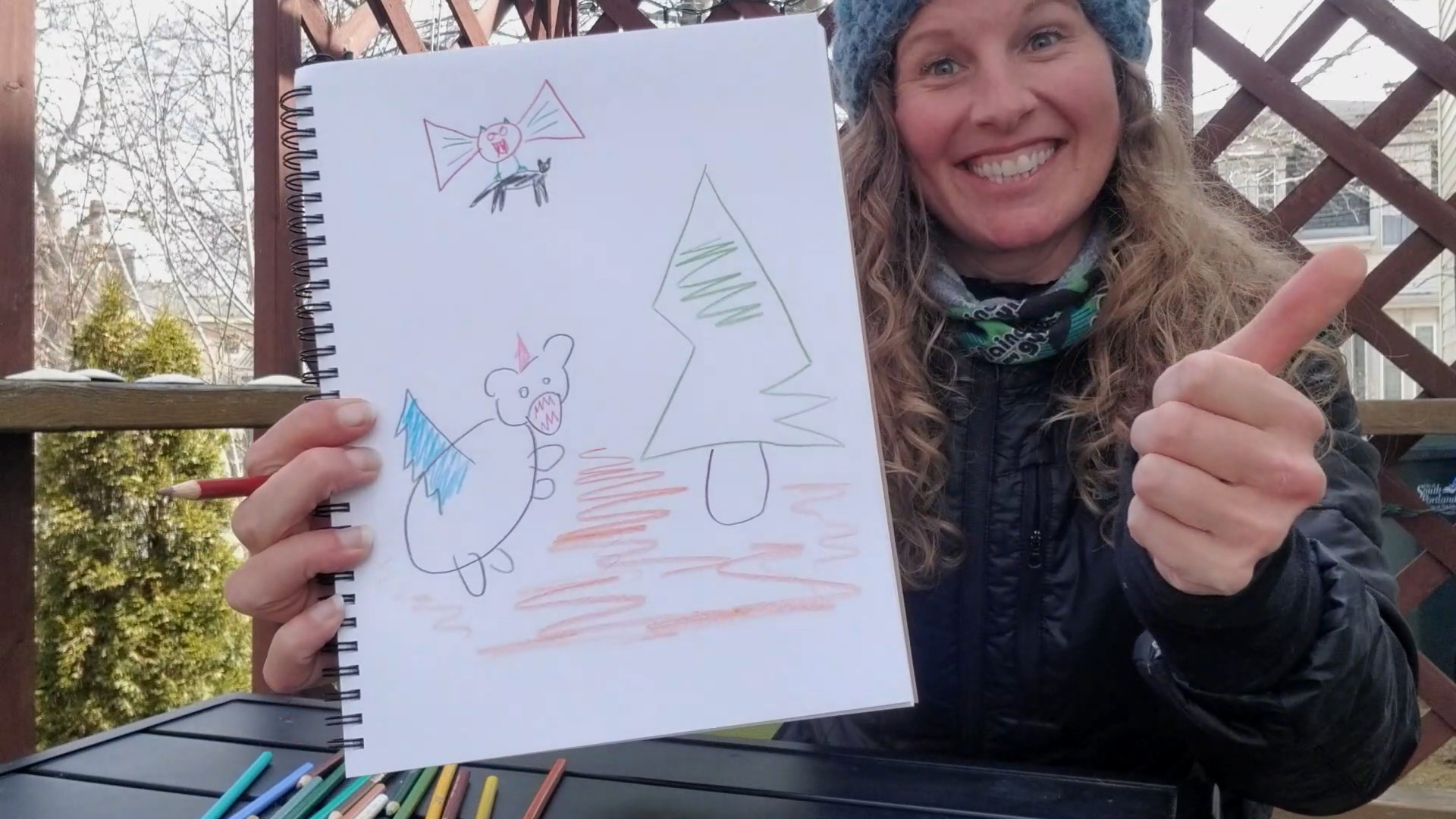 women holding sketchbook with poorly drawn animals on it